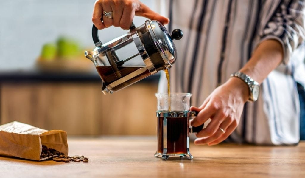 a lady pouring coffee through a french press