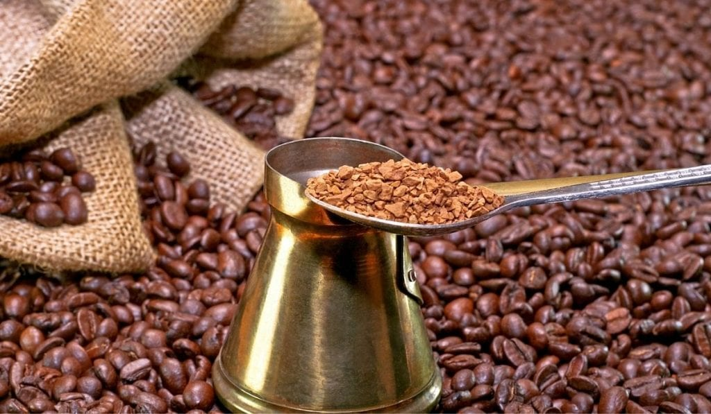 a teaspoon of instant coffee with coffee beans on the background
