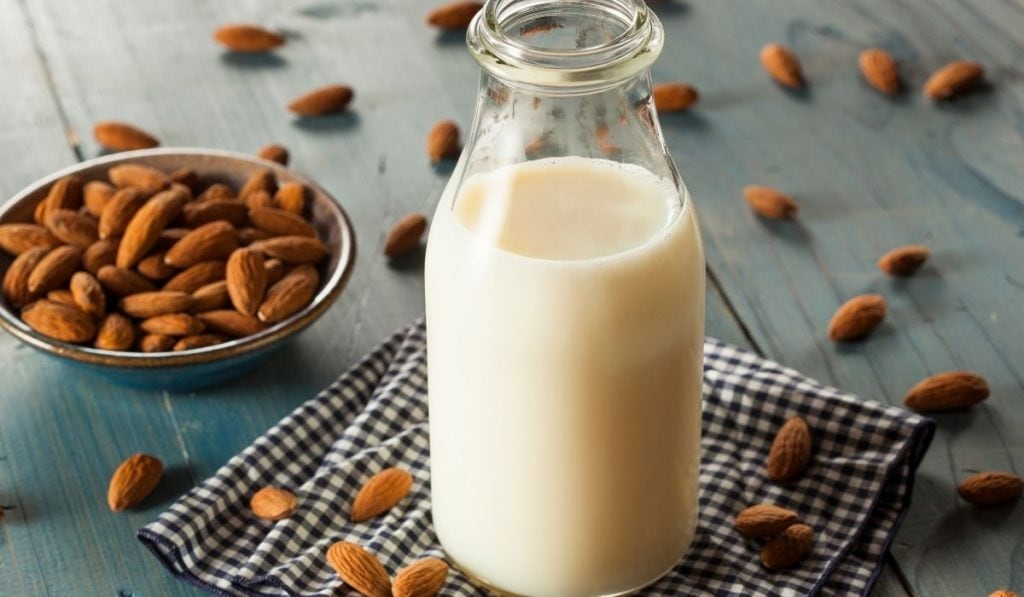 almond milk in a bottle with some almond nuts in a bowl