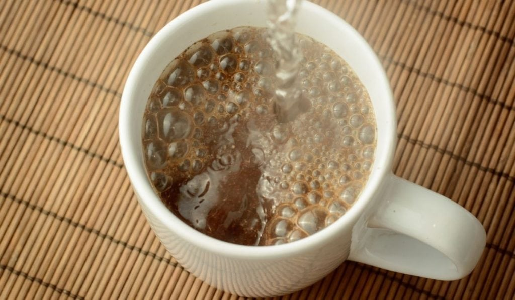 boiling water poured into a white cup with an instant coffee
