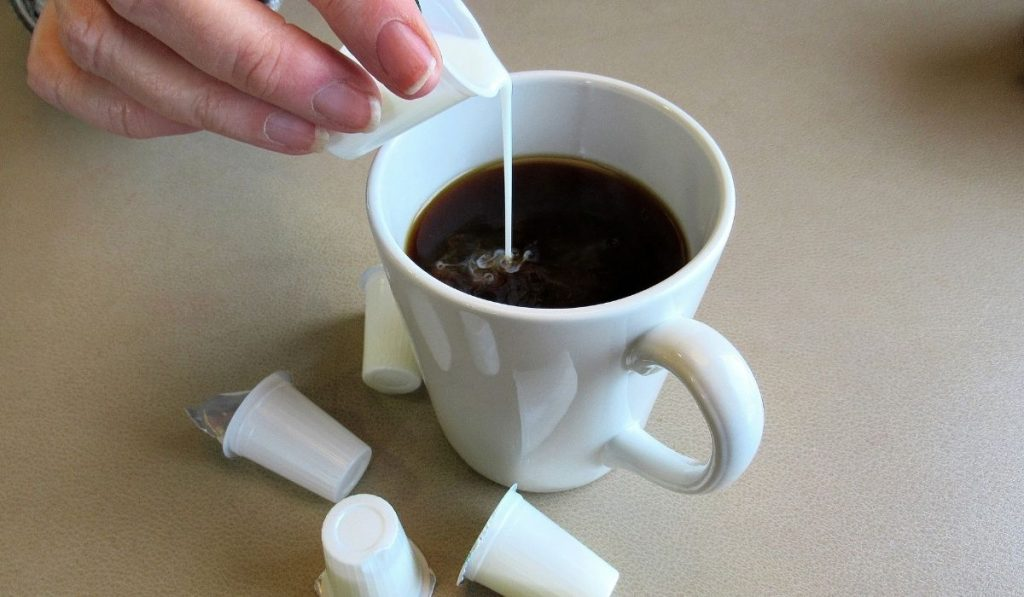 pouring a shot of creamer into a cup of black coffee