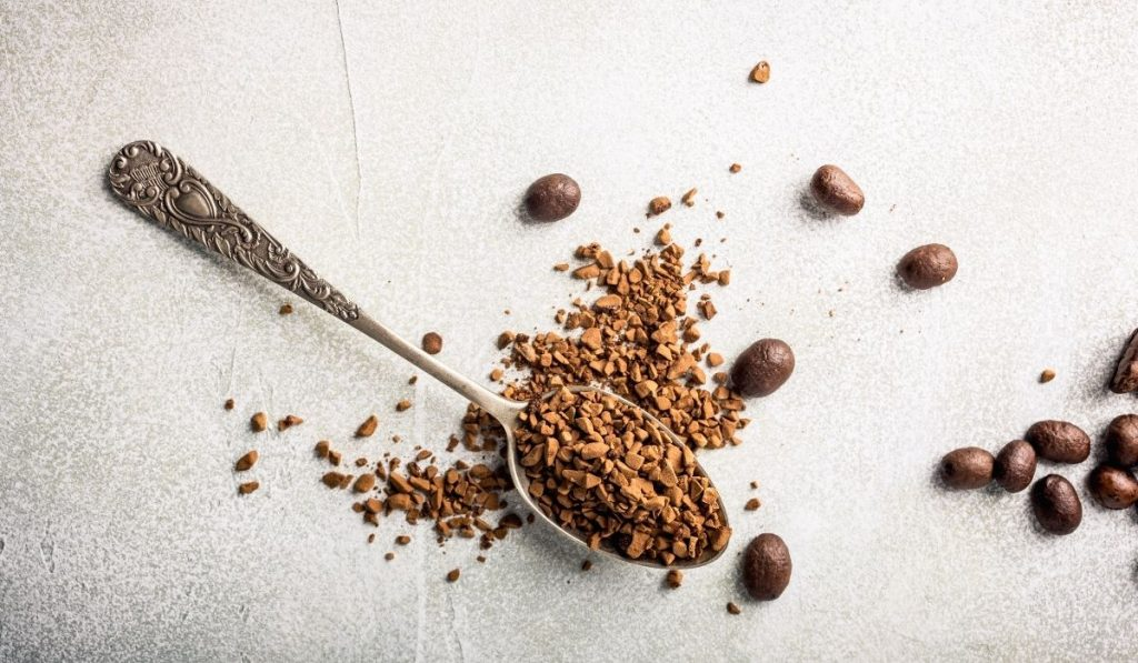 teaspoon of instant coffee with some coffee beans
