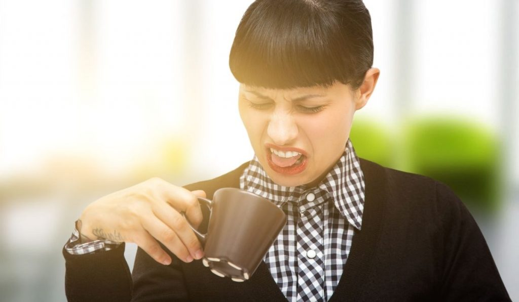 woman reacts bad while holding her coffee cup at work